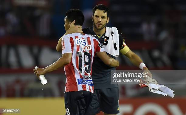 Colombias Atletico Junior player Teofilo Gutierrez and goalkeeper Mario Viera celebrate at the end of their match againts Peru's Alianza Lima during...