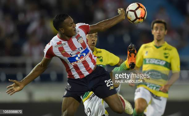 Colombia's Atletico Junior player Willer Ditta vies for the ball with Argentina's Defensa y Justicia player Nicolas Fernandez during a Copa...