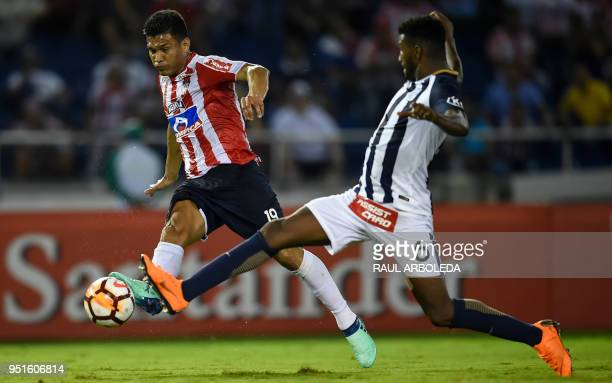 Colombia's Atletico Junior Teofilo Gutierrez is marked by Peru's Alianza Lima Carlos Ascues during their Copa Libertadores football match at the...