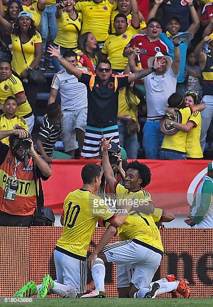 Colombia's Carlos Bacca celebrates with teammates James Rodriguez and Juan Cuadrado after scoring against Ecuador during their Russia 2018 FIFA World...