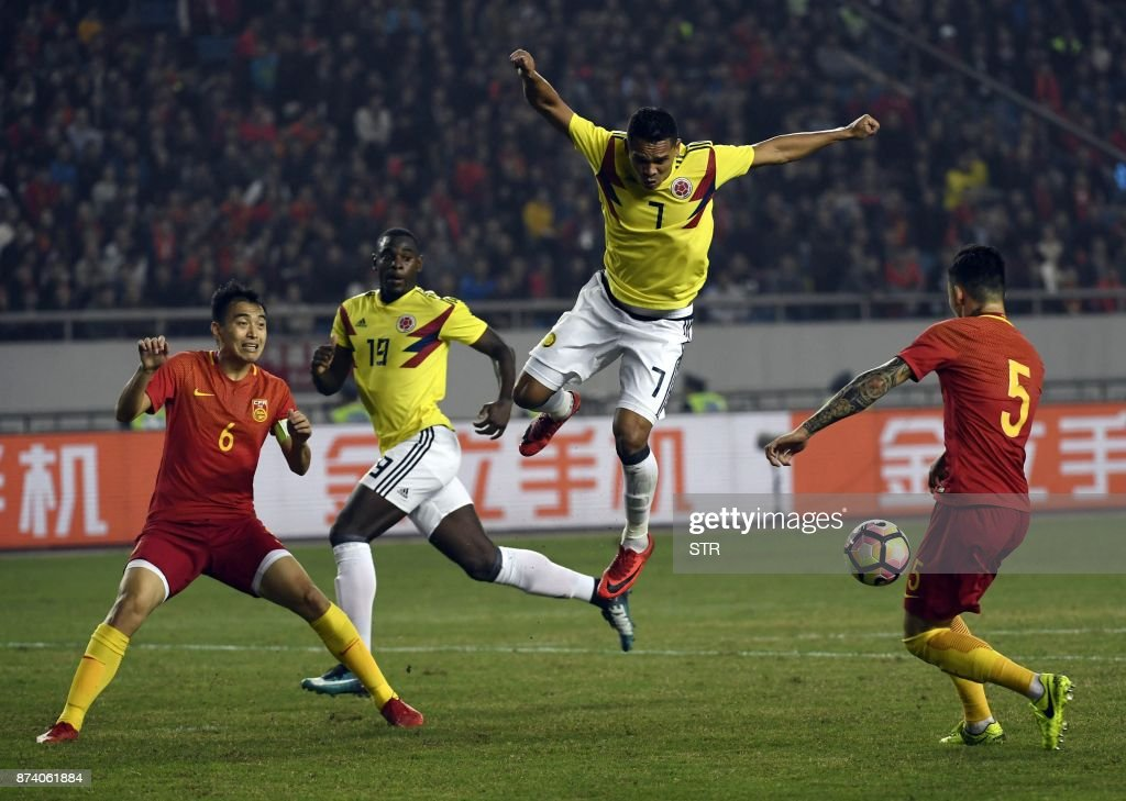 Colombia's Carlos Bacca (2R) fights for the ball with China's Zhang Linpeng (R) during their international friendly football match in Chongqing, southwest China on November 14, 2017. A Colombia side missing James Rodriguez punished China 4-0 away in a friendly on November 14 as coach Jose Pekerman made wholesale changes from the team defeated in acrimony in South Korea. / AFP PHOTO / STR / China OUT