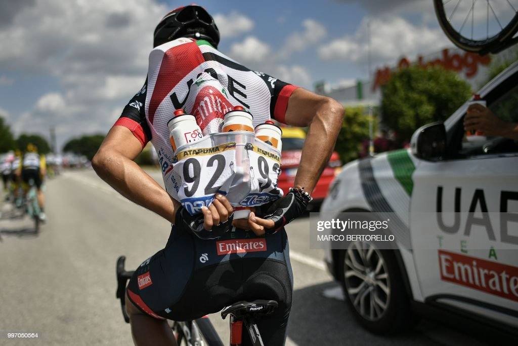 TOPSHOT - Colombia's Darwin Atapuma stacks water bottles for his teammates during the sixth stage of the 105th edition of the Tour de France cycling race between Brest and Mur-de-Bretagne Guerledan, western France, on July 12, 2018.