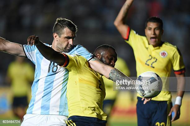 TOPSHOT Colombia's defender Eder Alvarez and Argentina's Lucas Pratto struggle for the ball during their 2018 FIFA World Cup qualifier football match...