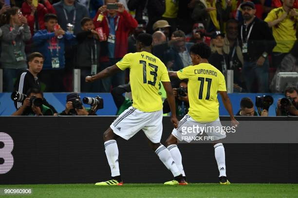 Colombia's defender Yerry Mina dances with Colombia's forward Juan Cuadrado after scoring a goal during the Russia 2018 World Cup round of 16...