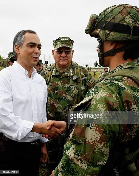 Colombia's Defense Minister Rodrigo Rivera , next to Colombian Armed Forces commander-in-chief, Admiral Edgar Cely , shakes hands with a soldier as...