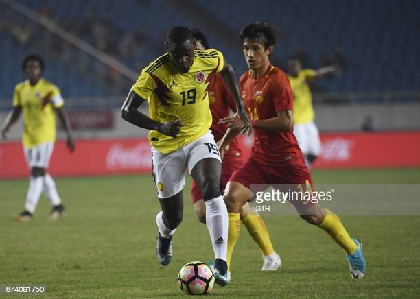 Colombia's Duvan Zapata fights for the ball with China's Wang Shenchao during their international friendly football match in Chongqing southwest...