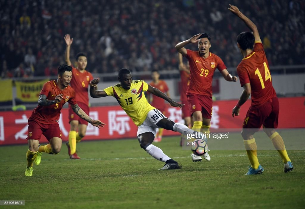 Colombia's Duvan Zapata (C, in yellow) fights for the ball with China's Zhang Linpeng (L) during their international friendly football match in Chongqing, southwest China on November 14, 2017. A Colombia side missing James Rodriguez punished China 4-0 away in a friendly on November 14 as coach Jose Pekerman made wholesale changes from the team defeated in acrimony in South Korea. / AFP PHOTO / STR / China OUT