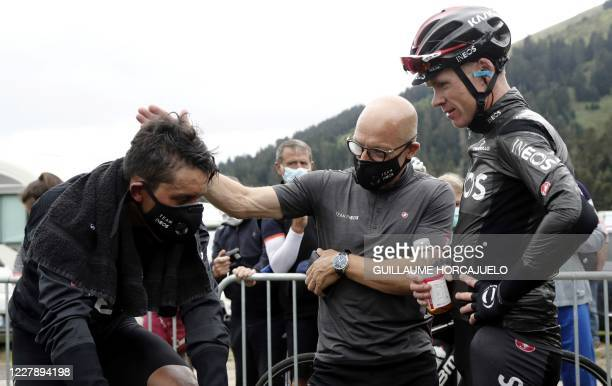 Colombia's Egan Bernal and Britain's Chris Froome and general manager Dave Brailsford of Team Ineos speak together as they celebrate after competing...