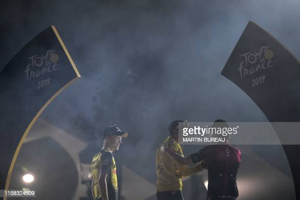 Colombia's Egan Bernal celebrates his overall leader's yellow jersey as he poses with secondplaced Great Britain's Geraint Thomas and thirdplaced...