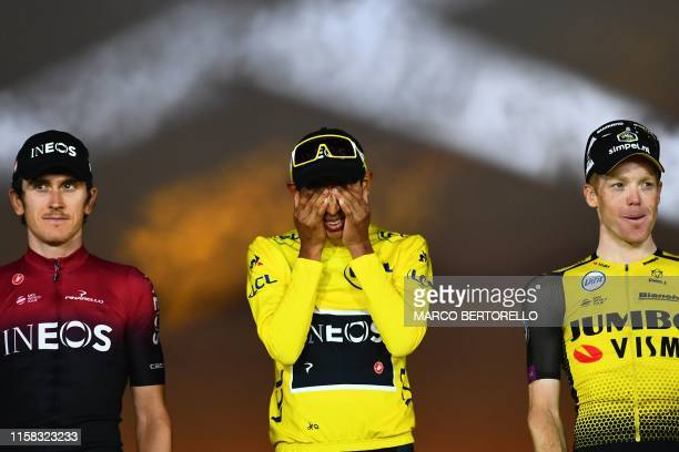 Colombia's Egan Bernal celebrates his overall leader's yellow jersey reacts as he poses with secondplaced Great Britain's Geraint Thomas and...
