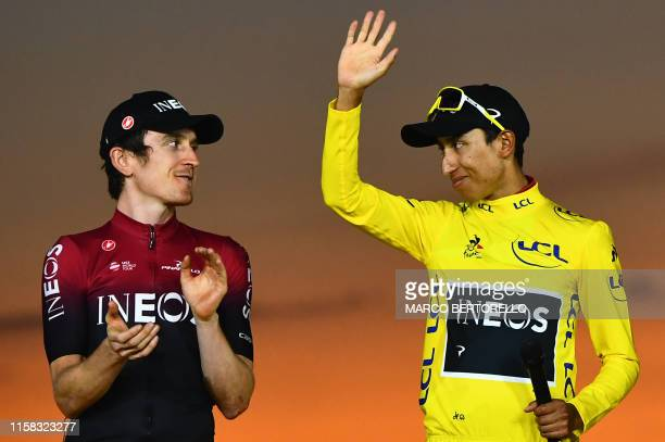 Colombia's Egan Bernal celebrates his overall leader's yellow jersey waves as he poses with secondplaced Great Britain's Geraint Thomas on the podium...