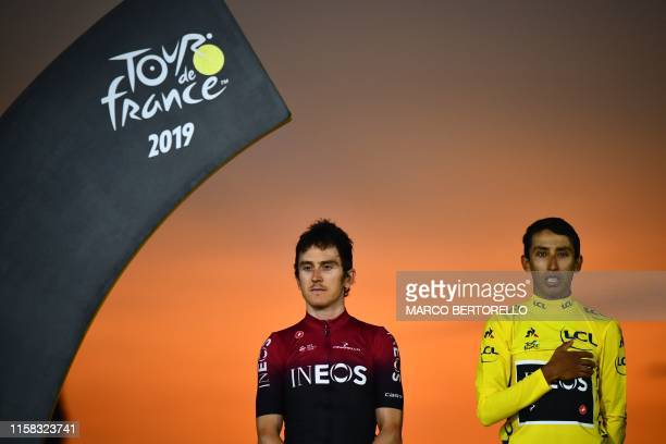Colombia's Egan Bernal listens to his national anthem after receiving his overall leader's yellow jersey past secondplaced Great Britain's Geraint...