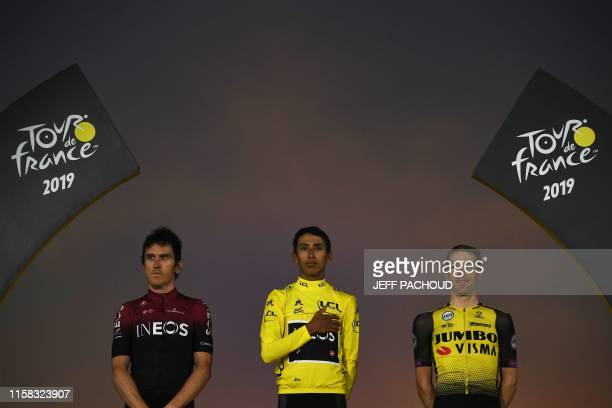 Colombia's Egan Bernal listens to his national anthem after receiving his overall leader's yellow jersey as he poses with secondplaced Great...
