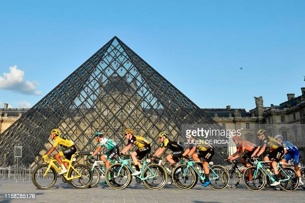 TOPSHOT Colombia's Egan Bernal of Team Ineos wears the overall leader's yellow jersey as he passes with the pack past the pyramid of The Louvre...