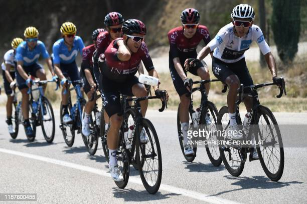 Colombia's Egan Bernal , wearing the best young's white jersey throws a bidon past Great Britain's Geraint Thomas as they ride with teammates during...