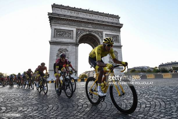 TOPSHOT Colombia's Egan Bernal wearing the overall leader's yellow jersey and cyclists ride down the Champs Elysees avenue next to the Arc de...