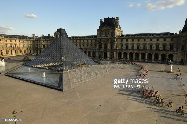 Colombia's Egan Bernal wearing the overall leader's yellow jersey passes with the peloton by the Louvre pyramid designed by Ieoh Ming Pei and the...
