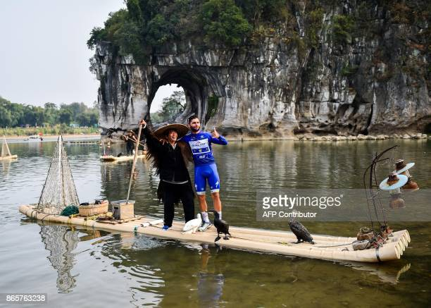 Colombia's Fernando Gaviria of team QuickStep Floors poses for photographs with a Chinese fishman in front of the Elephant Trunk Hill a famous scenic...