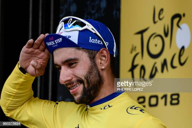 Colombia's Fernando Gaviria wearing the overall leader's yellow jersey celebrates on the podium after winning the first stage of the 105th edition of...