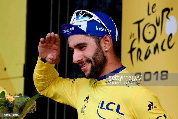 Colombia's Fernando Gaviria, wearing the overall leader's yellow jersey, celebrates on the podium after the first stage of the 105th edition of the...