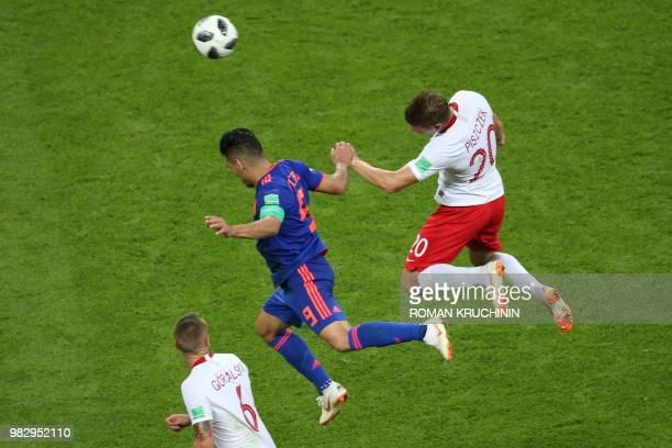 TOPSHOT Colombia's forward Falcao heads the ball with Poland's defender Lukasz Piszczek during the Russia 2018 World Cup Group H football match...