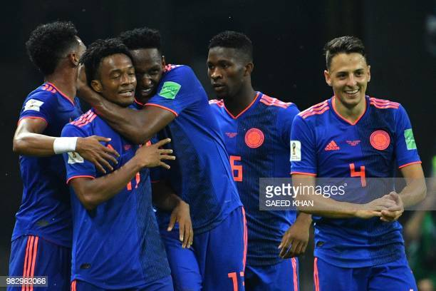 Colombia's forward Juan Cuadrado celebrates with teammates after scoring their third goal during the Russia 2018 World Cup Group H football match...