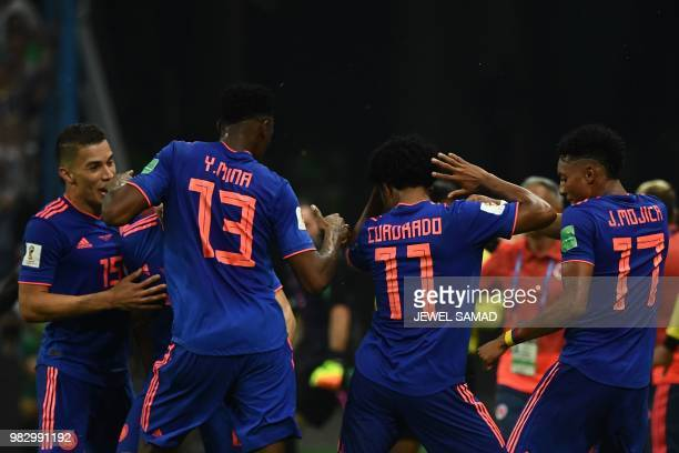 TOPSHOT Colombia's forward Juan Cuadrado celebrates with teammates after scoring during the Russia 2018 World Cup Group H football match between...