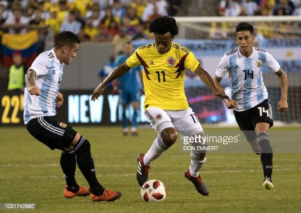 Colombia's fowardJuan Guillermo Cuadrado controls the ball next to from Argentina's defender Fabricio Bustos and foward Angel Correa during the...
