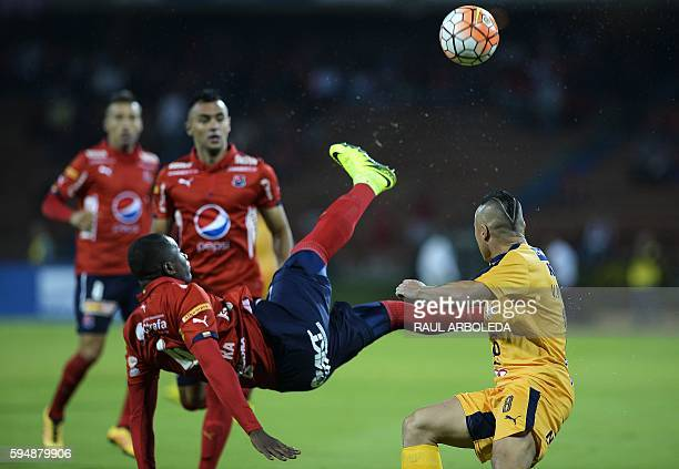 Colombia's Independiente Medellin player Andres Mosquera vies for the ball with Paraguay's Sportivo Luqueno player Vladimir Marin during their Copa...