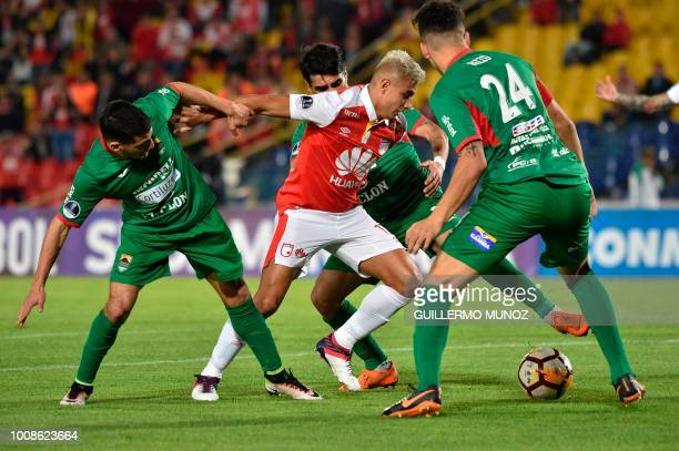 Colombia's Independiente Santa Fe forward Juan Roa and Uruguay's Rampla Juniors players vie for the ball during their Copa Sudamericana football...