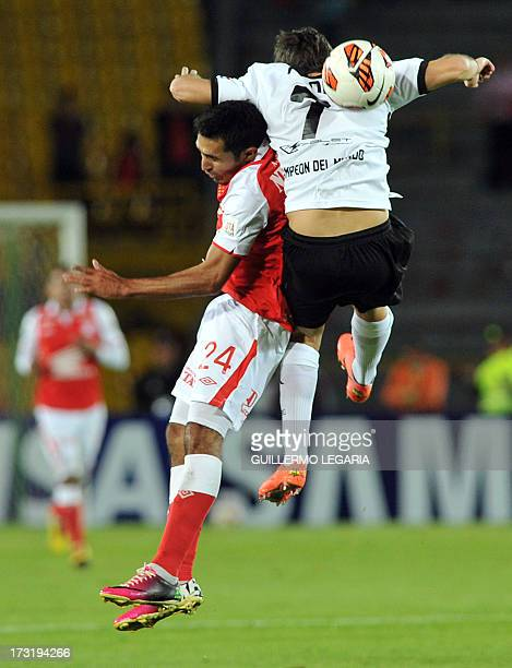 Colombia's Independiente Santa Fe player Hugo Acosta vies for the ball with Enzo Prono of Paraguay's Olimpia during their 2013 Copa Libertadores...