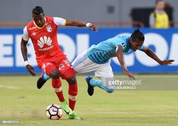 Colombias Independiente Santa Fe player Johan Arango vies for the ball with Peru's Sporting Cristal Pedro Aquino during their Copa Libertadores...