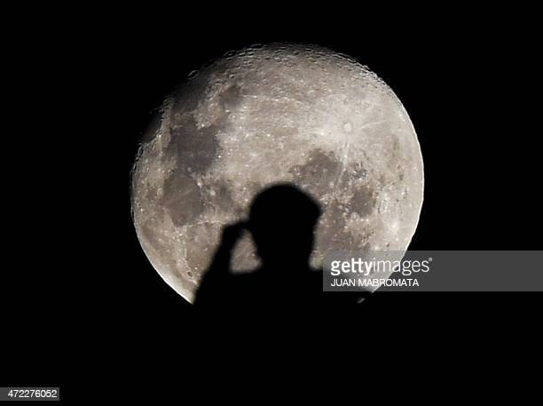 A Colombia's Independiente Santa Fe supporter is silohuetted against the almost full moon at Ciudad de La Plata stadium during the Copa Libertadores...