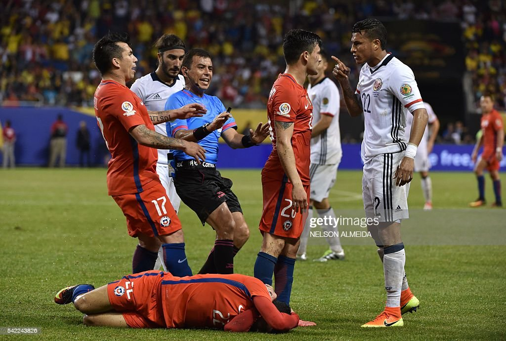 TOPSHOT - Colombia's Jeison Murillo (R) argues with Chile's Charles Aranguiz (2-R) as Chile's Edson Puch lies on the field next to Salvadorean referee Joel Aguilar (C) during a Copa America Centenario semifinal football match in Chicago, Illinois, United States, on June 22, 2016. / AFP / Nelson ALMEIDA