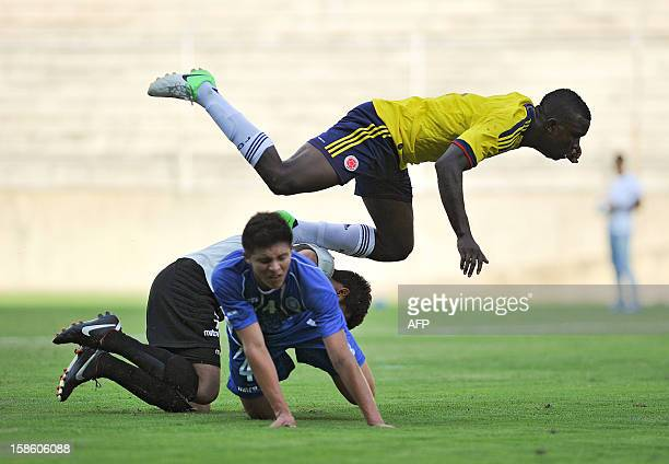 Colombia's John Cordoba jumps over El Salvador's Giovanni Zabaleta and Morales Rolando during a friendly football match on December 20 in Cali...