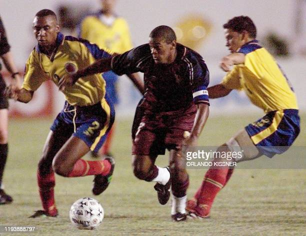 Colombia's John Viafara and Luis Arce try to stop Venezuela's Jorge Rojas 21 January during the Sydney 2000 Olympic qualifying tournament in Brazil...
