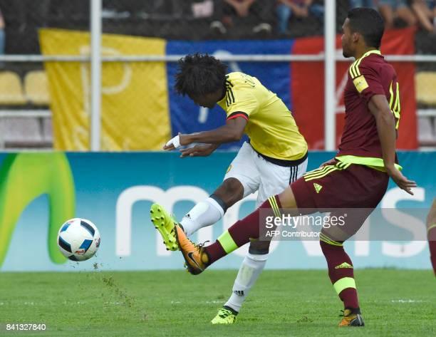 Colombia's Juan Cuadrado is marked by Venezuela's Yangel Herrera during their 2018 World Cup qualifier football match in San Cristobal Venezuela on...