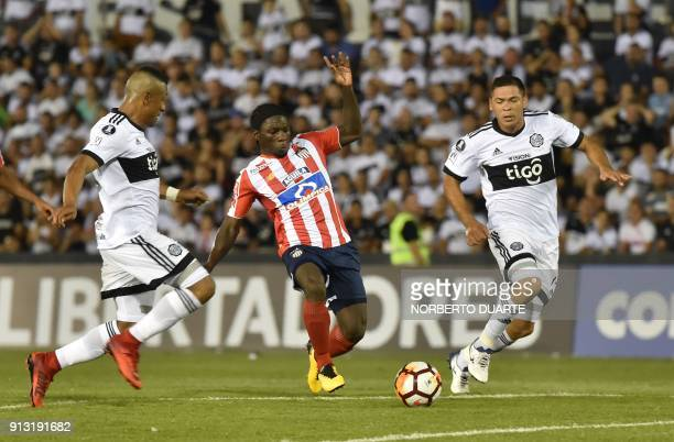 Colombia's Junior player Yimmi Chara vies for the ball with Paraguay's Olimpia players Farid Diaz and Juan Patino during their Libertadores Cup...