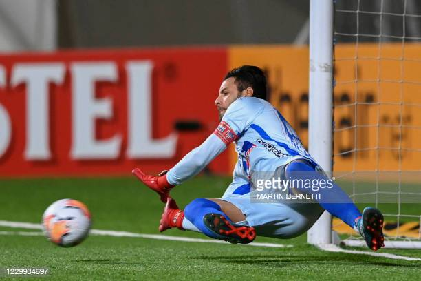 Colombia's Junior Uruguayan goalkeeper Sebastian Viera dives to stop a ball during the penalty shootout of the closed-door Copa Sudamericana round...