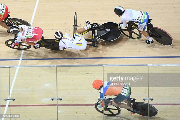 TOPSHOT Colombia's Martha Bayona Pineda falls off her bike after crashing during the women's Keirin second round track cycling event at the Velodrome...