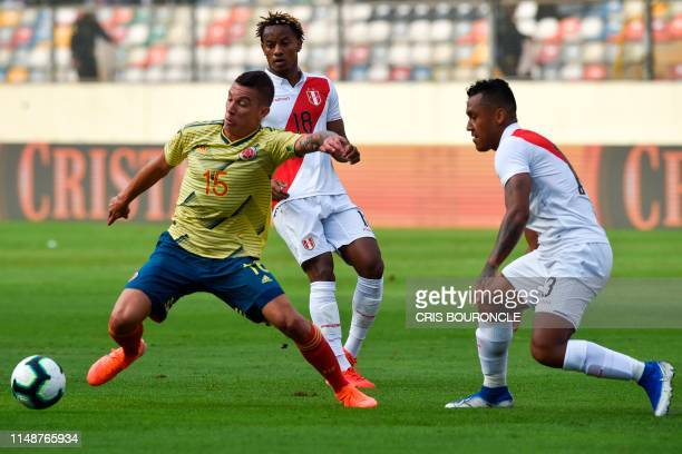 Colombia's Mateus Uribe dribbles past Peru's Aldo Corzo and Peru's Andre Carrillo during a friendly football match between Peru and Colombia at the...