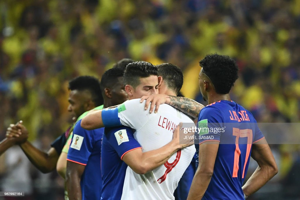 TOPSHOT - Colombia's midfielder James Rodriguez (L) hugs Poland's forward Robert Lewandowski at the end of the Russia 2018 World Cup Group H football match between Poland and Colombia at the Kazan Arena in Kazan on June 24, 2018. Colombia won 0-3. (Photo by Jewel SAMAD / AFP) / RESTRICTED
