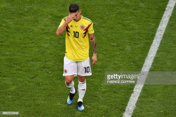TOPSHOT Colombia's midfielder James Rodriguez reacts as he leaves the football pitch due to an injury during the Russia 2018 World Cup Group H...