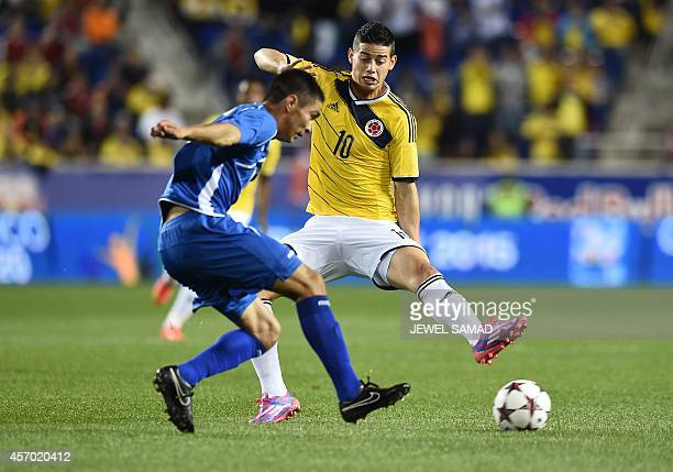 Colombia's midfielder James Rodriguez vies for the ball with El Salvador midfielder Nestor Renderos during their friendly match at the Red Bull Arena...