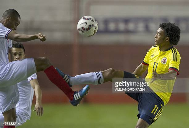 Colombia's midfielder Juan Cuadrado vies for the ball with Costa Rica's defender Junior Diaz during a friendly football match at Diego Armando...