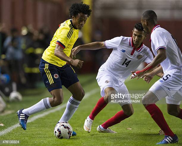 Colombia's midfielder Juan Cuadrado vies for the ball with Costa Rica's defender Junior Diaz and midfielder Deyver Vega during a friendly football...