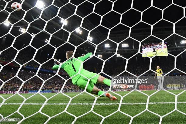 TOPSHOT Colombia's midfielder Mateus Uribe misses to score a penalty kick as England's goalkeeper Jordan Pickford jumps to catch the ball during the...