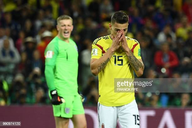 TOPSHOT Colombia's midfielder Mateus Uribe reacts after missing to score a penalty kick next to England's goalkeeper Jordan Pickford celebrating...