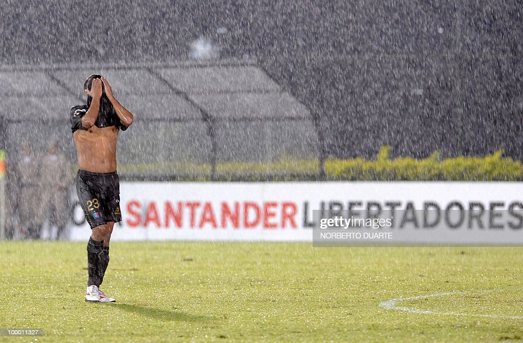 Colombia's Once Caldas player Jaime Castrillon leaves the field dejectedly amid a downpour after losing to Paraguay's Libertad in their Libertadores Cup football match on May 06, 2010 in Asuncion, Paraguay. AFP PHOTO / Norberto Duarte