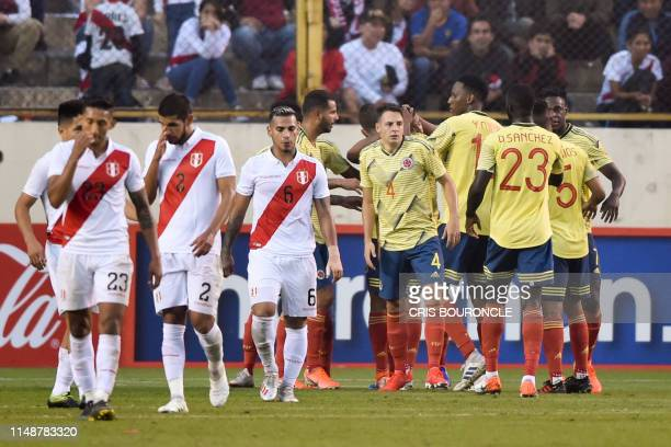 Colombia's players celebrate after defeating Peru 3-0 as Peru's players react at the end of a friendly football match at the Monumental Stadium in...